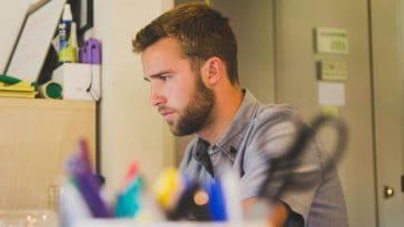 jeune homme réfléchit devant ordinateur dossier job etudiant
