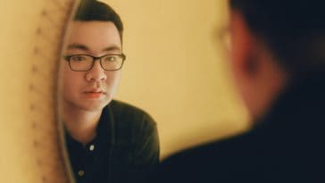 pexels-min-an-étudiant qui se regarde dans le miroir Ces choses qui te montrent que t'as pris un coup de vieux