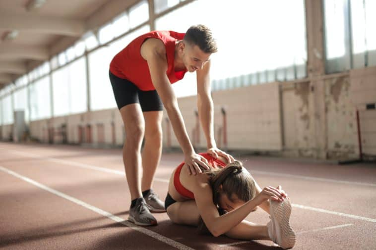 pexels-andrea-piacquadio-couple etudiant qui s'étirent - Faire du sport en couple 5 exercices à faire à deux