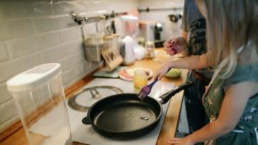 pexels-daria-obymaha-fille dans une cuisine avec une poele - top 10 des ustensiles de cuisine